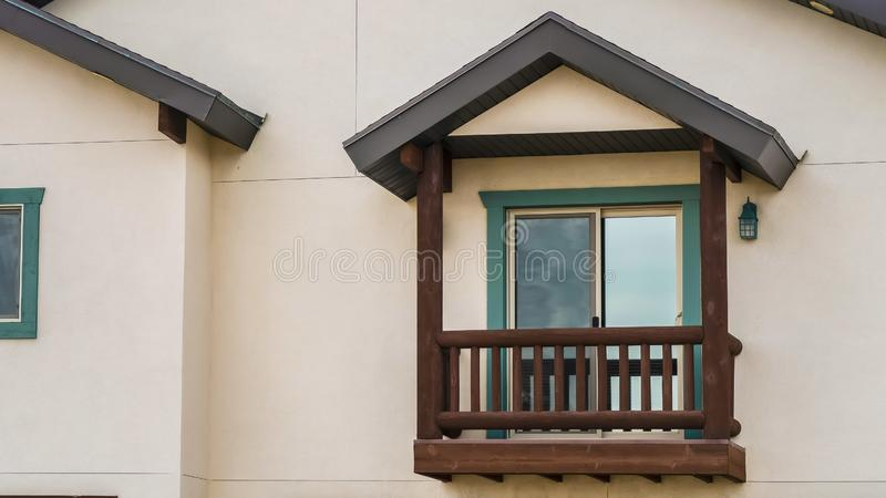 Panorama frame Small balcony with brown wooden railings and posts under a pitched roof. Panorama Small balcony with brown wooden railings and posts under a royalty free stock photography