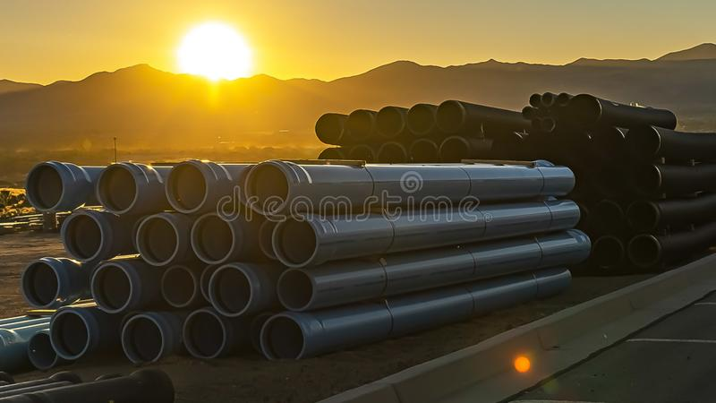 Panorama frame Stack of pipes with a golden sun setting behind a mountain in the background royalty free stock photos
