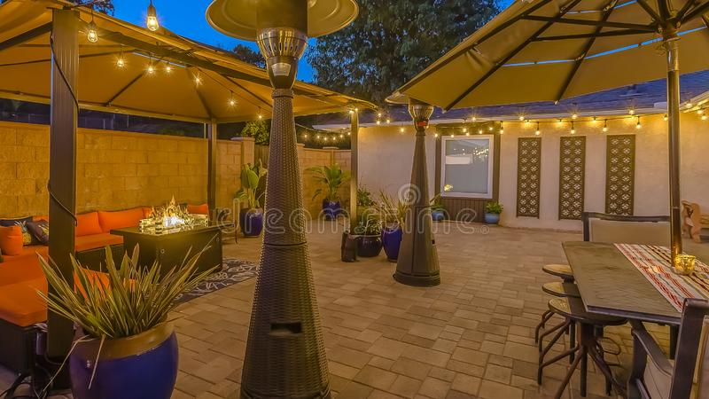 Panorama frame Stone brick patio of a home illuminated with string lights and lamp posts. The open air dining area is under an umbrella while the seating area royalty free stock images