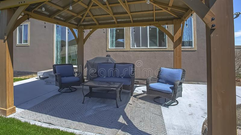 Panorama frame Table and chairs at a patio shaded by a pavilion with string of light bulbs royalty free stock photos