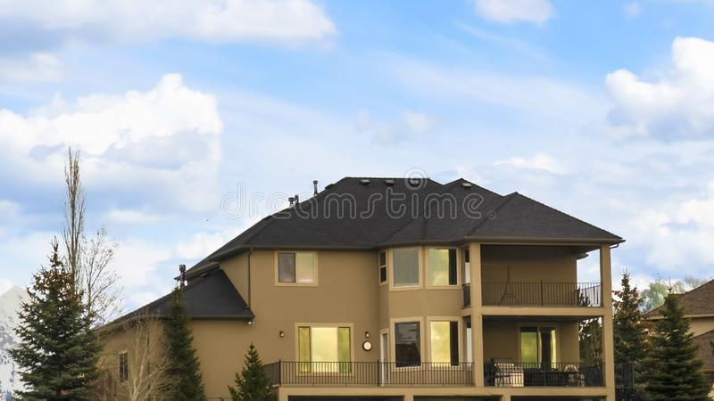 Panorama frame Three storey home with porch and balcony against blue sky with bright clouds. Coniferous trees and snow covered ground can be seen outside the stock images