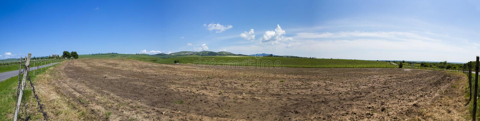 Panorama of a fresh ploughing agriculture field. And a graveyard in the background from Romania stock photo