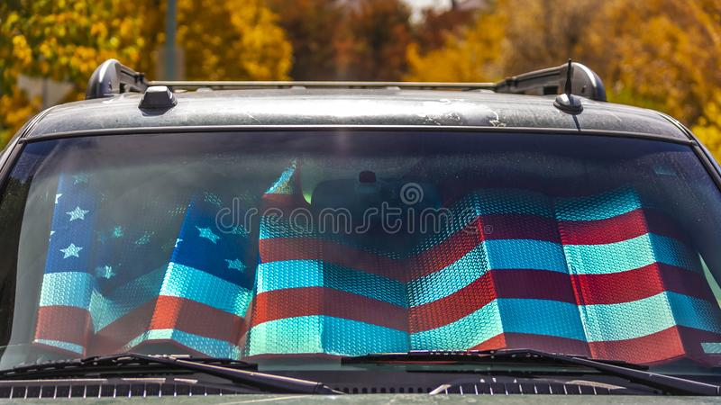Panorama Front view of a shiny gray vehicle against lush trees on a sunny autumn day. Inside the vehicle is a sunshade with an American flag design stock photo