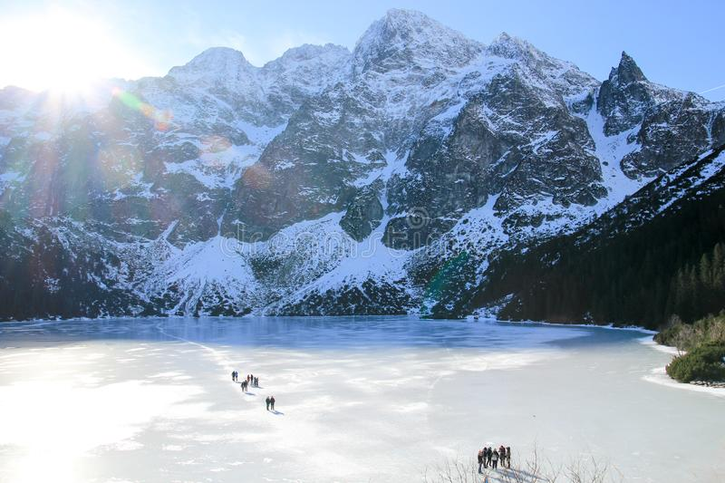 Panorama of frozen lake surrounded by mountains. People walk on. The ice stock photos