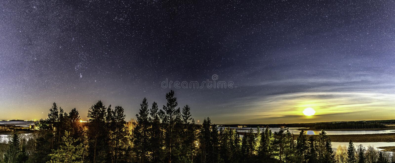 Panorama of full moon and stars in clear sky shines over Scandinavian wild forest, lakes, swamps, long exposure night photo, stock photography