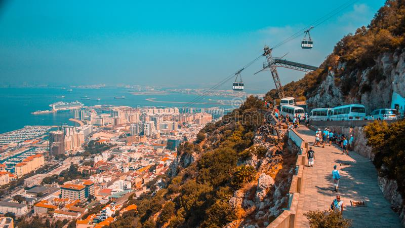 Panorama of Gibraltar. With `Rock of Gibraltar` and Gibraltar cableway and tourists buses in orange&teal color grade stock images