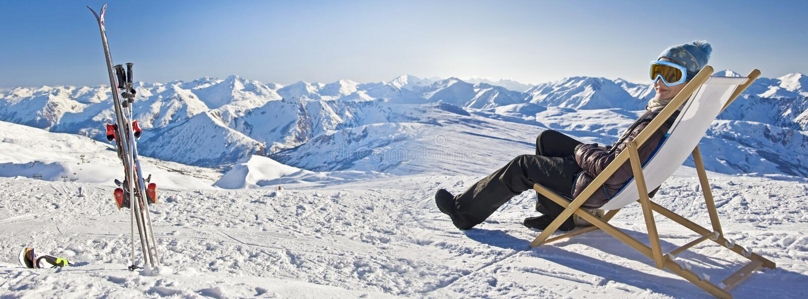Panorama of a girl sunbathing in a deckchair near a snowy ski slope. Panorama of a girl sunbathing in a deckchair near a ski slope royalty free stock images