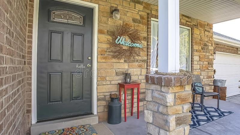 Panorama Glass paned front door and stone brick exterior wall at the facade of a home. A seating area, Welcome wreath, and ornaments can be seen on the small royalty free stock image