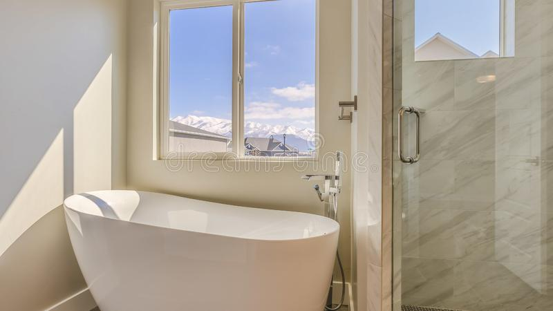 Panorama Glossy bathtub and separate shower inside the sunlit bathroom of a new house. The sliding window provides a scenic view of houses, snow capped royalty free stock photography