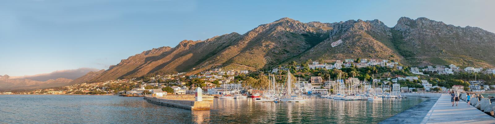 Panorama of Gordons Bay harbor and Hottentots-Holland Mountains. CAPE TOWN, SOUTH AFRICA - DECEMBER 11, 2014: Sunset panorama of the harbor in Gordons Bay with stock photos