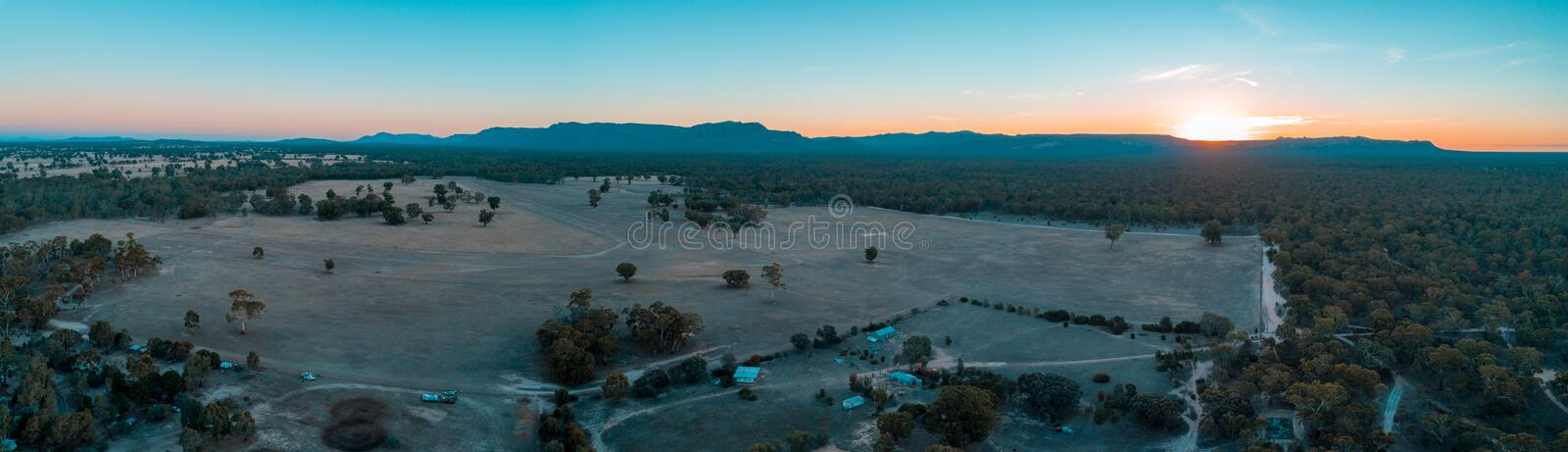 Panorama of Grampians mountains, farmland, and forest. Wide aerial panorama of Grampians mountains, farmland, and forest at sunset. Victoria, Australia royalty free stock image