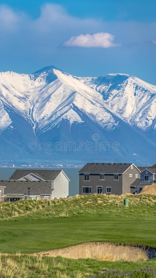 Panorama Grassy hill with houses overlooking a vast lake and snow capped mountain. Cloudy blue sky cna be seen over the valley on this sunny day royalty free stock photo
