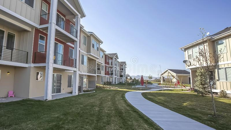 Panorama Grassy terrain and pathway in front of houses under blue sky on a sunny day. The residential buildings have small porches and balconies royalty free stock photos