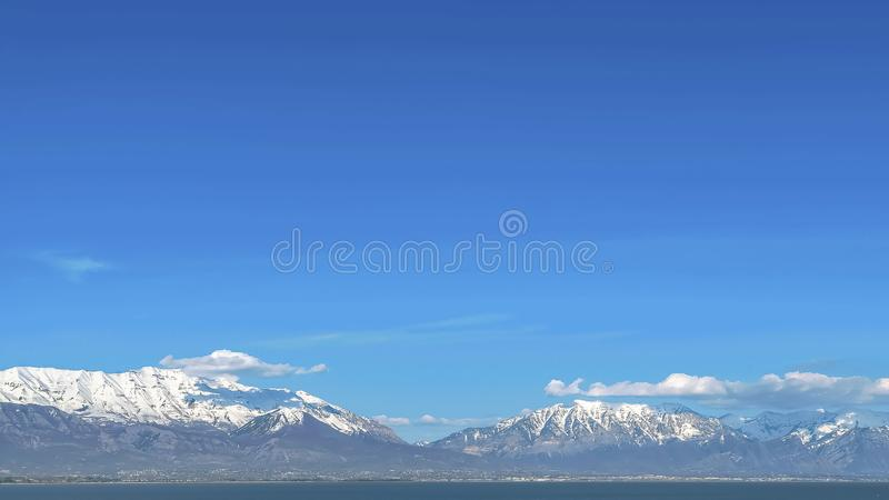 Panorama Grassy terrain with view of lake and snowy mountain under blue sky on sunny day. Brown grasses grow on the shallow parts of the water royalty free stock image