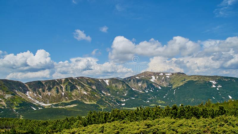 Panorama of the green hills and snow in Carpathian mountains with the blue sky and white clouds stock images