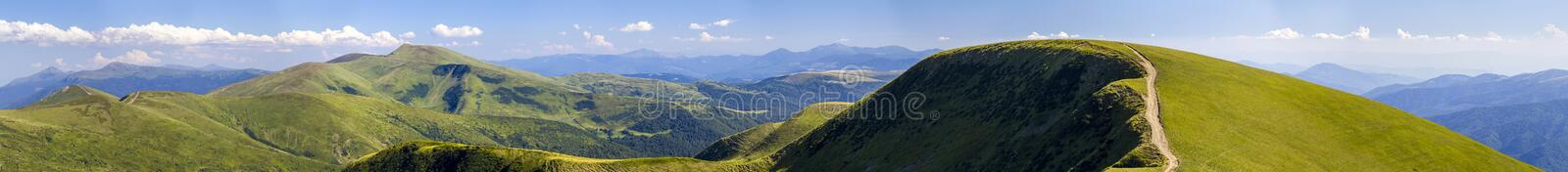 Panorama of green hills in summer mountains with gravel road for royalty free stock photos