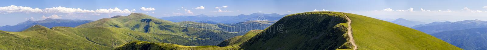 Panorama of green hills in summer mountains with gravel road for stock photo