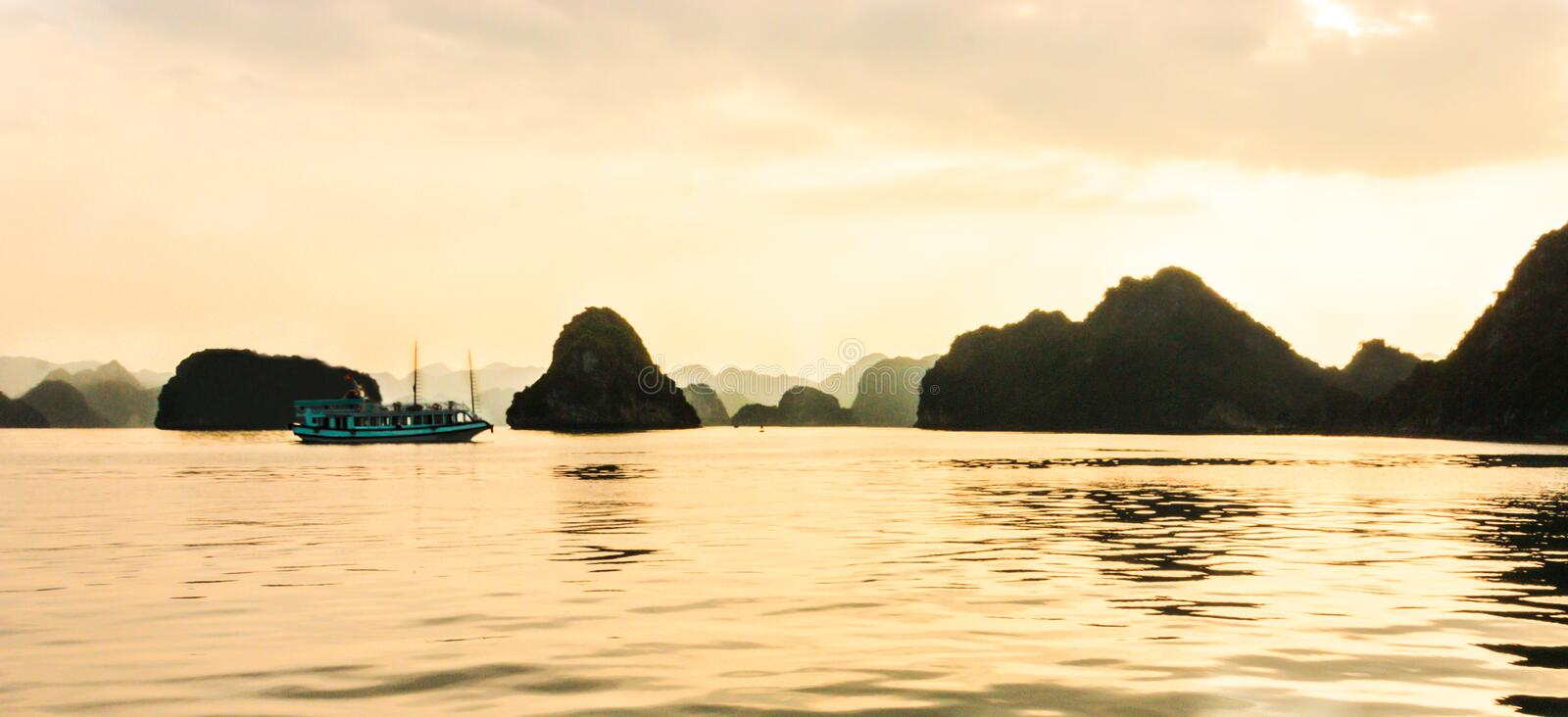 Panorama of Ha Long bay islands, tourist boat and seascape in the evening with golden light reflection on water, Ha Long, Vietnam royalty free stock photos