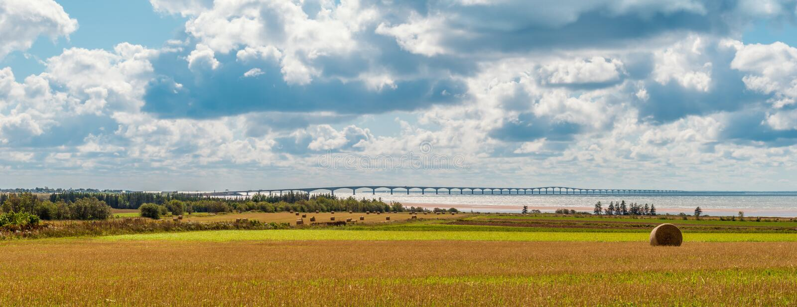 Panorama of hay bales on a farm along the ocean with the Confederation Bridge in the background. (Prince Edward Island, Canada stock image