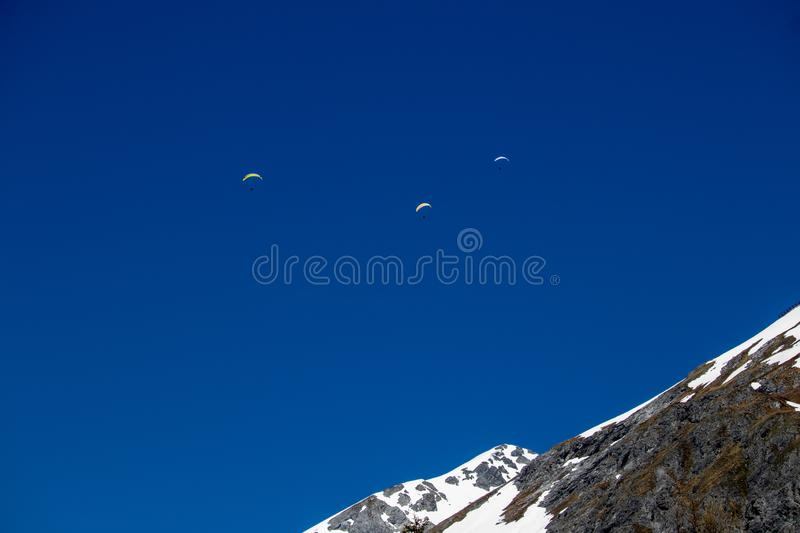 Panorama of high partly snowy mountains with paragliders stock photo
