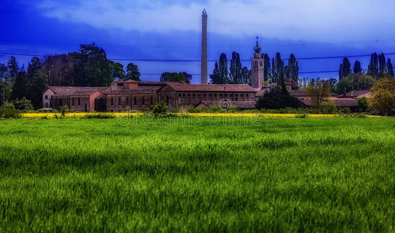 Panorama with high saturation of green field colors with church in the background, Campocroce di Mogliano Veneto Treviso.  stock photography