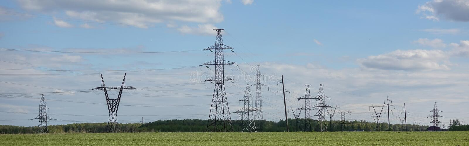 Panorama of high voltage substation. Distribution electrical power. Silhouettes of pylons and towers stock photos