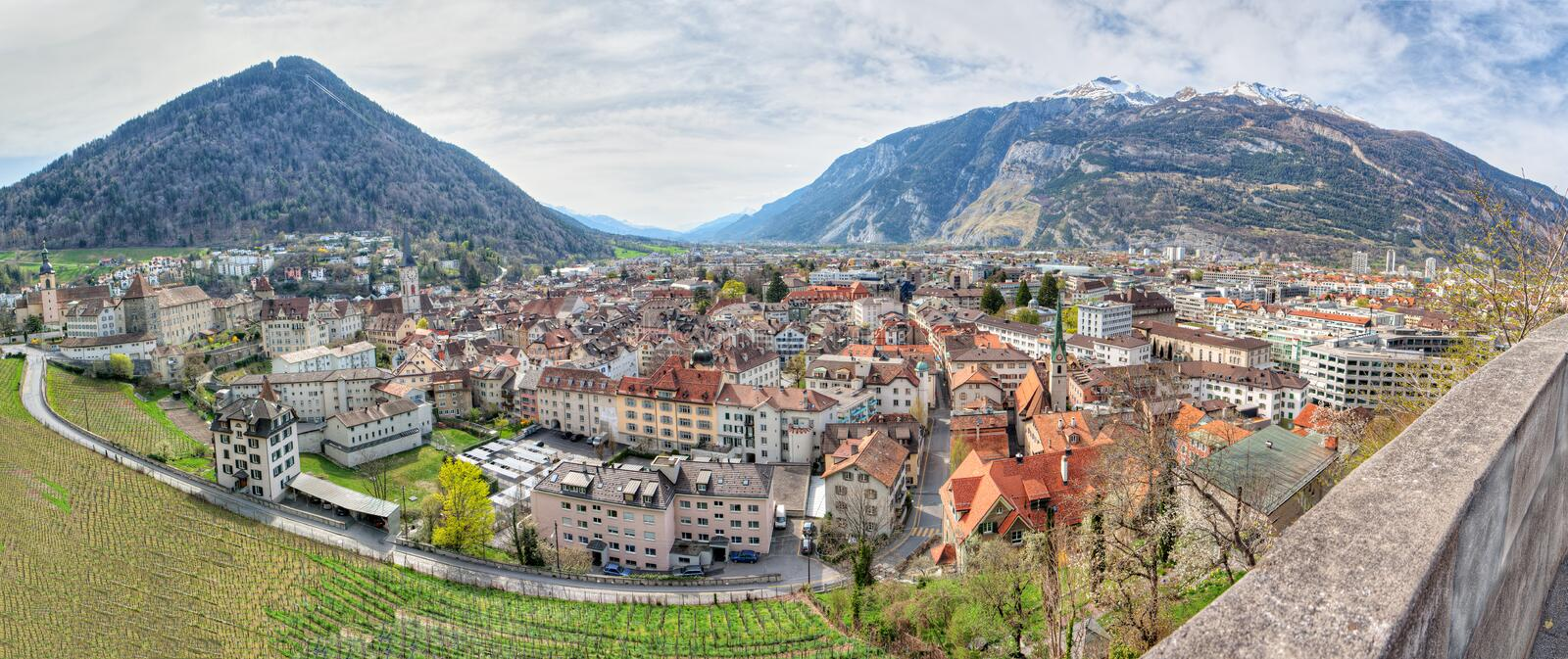 Panorama of historic Chur, Switzerland. Panorama of historic city center with church, castle and old houses surrounded by vinyards and mountains in Chur stock image