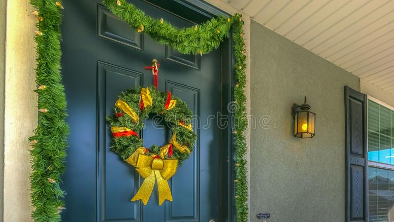 Panorama Home with a sunlit porch and front door decorated with wreath and garland. The scenic mountain and vibrant blue sky are reflected on the sliding glass stock photography