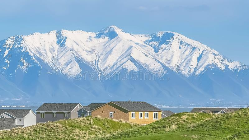 Panorama Homes and grassy field with snow covered mountain and blue sky background. A lake and valley cna also be seen on this picturesque landscape stock image