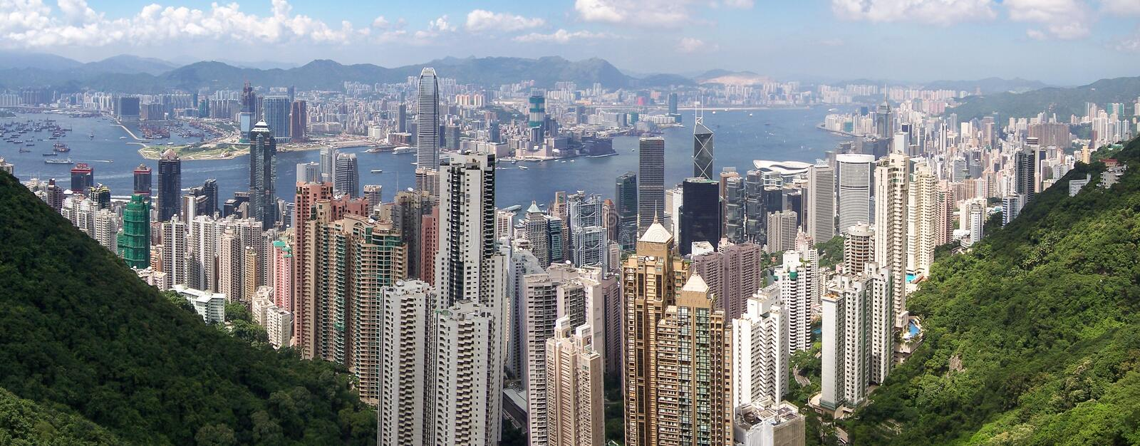 Panorama of Hong Kong etween hills and the harbor from Victoria Peak China. Panorama view of Hong Kong city and the harbor on cloudy day stock photo