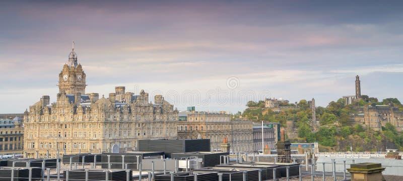 Panorama- horisontsikt för Edinburg i solnedgången, historiska byggnader Inklusive Edinburgslott torn för Balmoral hotellklocka arkivbilder