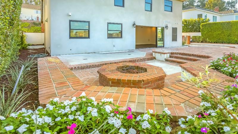Panorama House with a stone brick patio and octagonal fire pit made of the same material. Tall hedges and flowering plants surround the rustic outdoor space stock images
