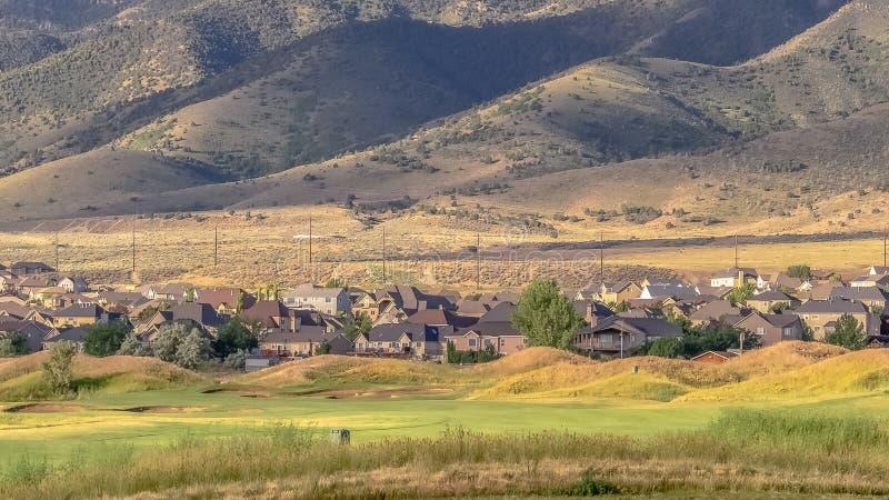 Panorama incorniciata Fairway e verde di un campo da golf con case per una montagna fotografie stock
