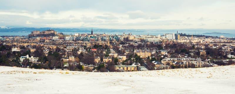 Panorama innevato di Edimburgo, compreso il castello ed il sedile di Arthurs immagini stock