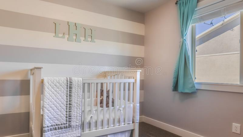 Panorama Interior of a nursery with white crib and monogram letters on the striped wall. Sunlight streaming through the large window provides natural lighting stock photo