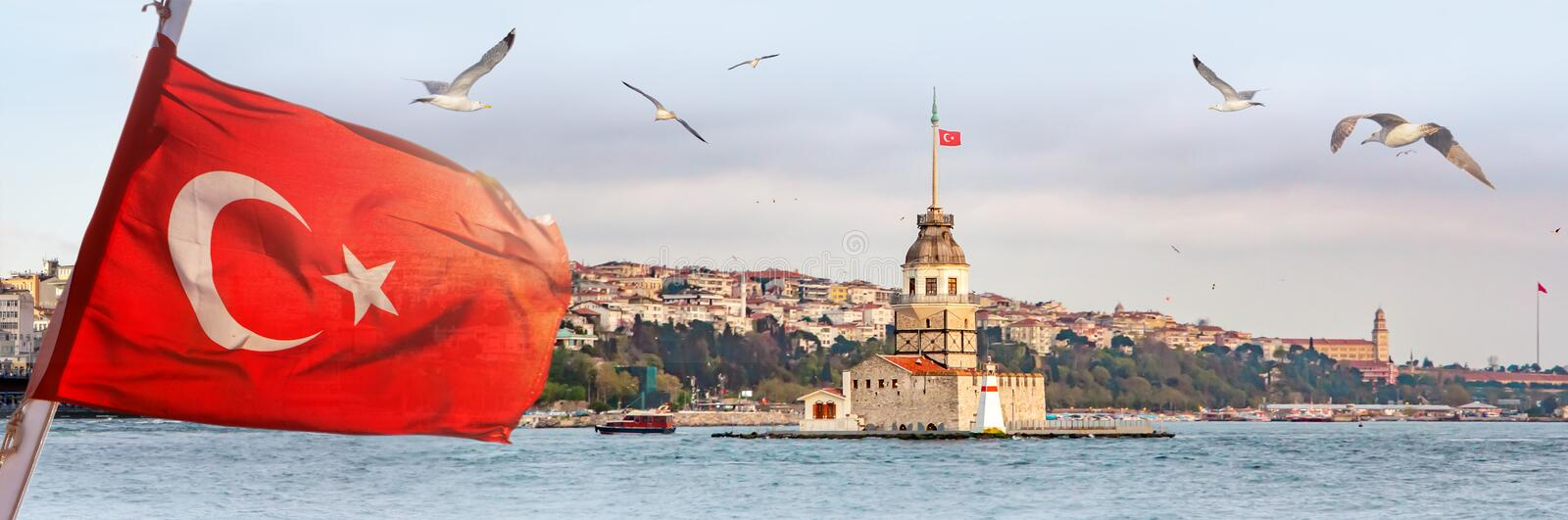 Panorama of Istanbul with Maiden Tower, kiz kulesi, at skyline and seagulls over the sea, wide landscape with the Turkish flag in. The foreground, travel royalty free stock photo