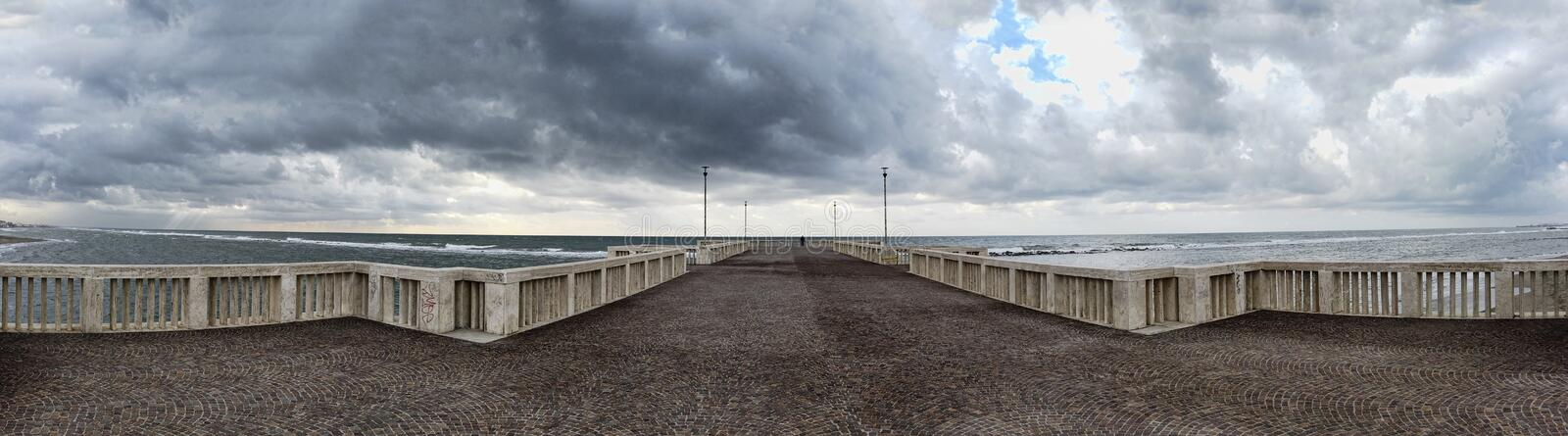 Panorama from the jetty to rough sea with scenic sky covered by clouds ready for the rain at distance a man alone looking the sea royalty free stock photos