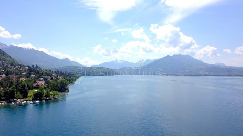 Panorama jezioro, g?ry i cha?upy, zbli?amy brzeg akcja Odg?rny widok malowniczy b??kitny jezioro, brzeg z cha?upami dla obraz royalty free