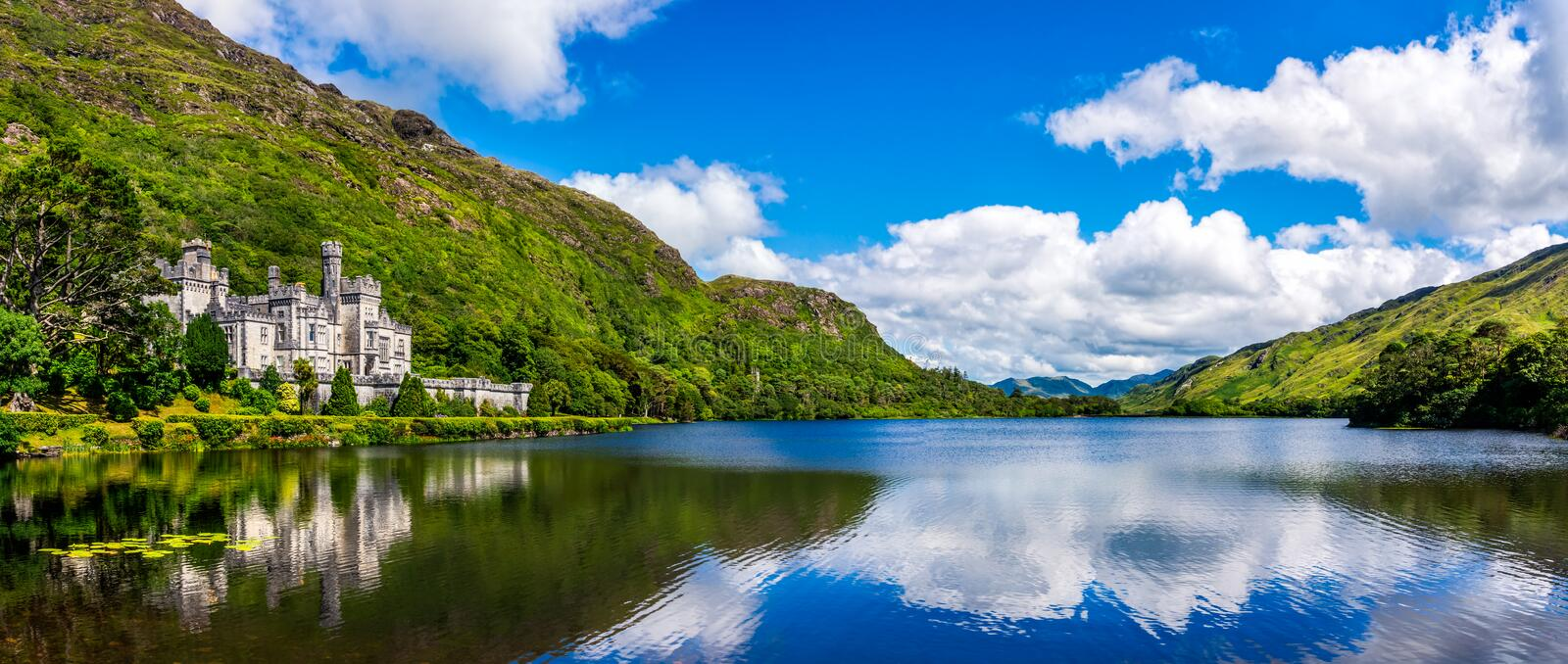 Kylemore Abbey, beautiful castle like abbey reflected in lake at the foot of a mountain. Ireland royalty free stock photo