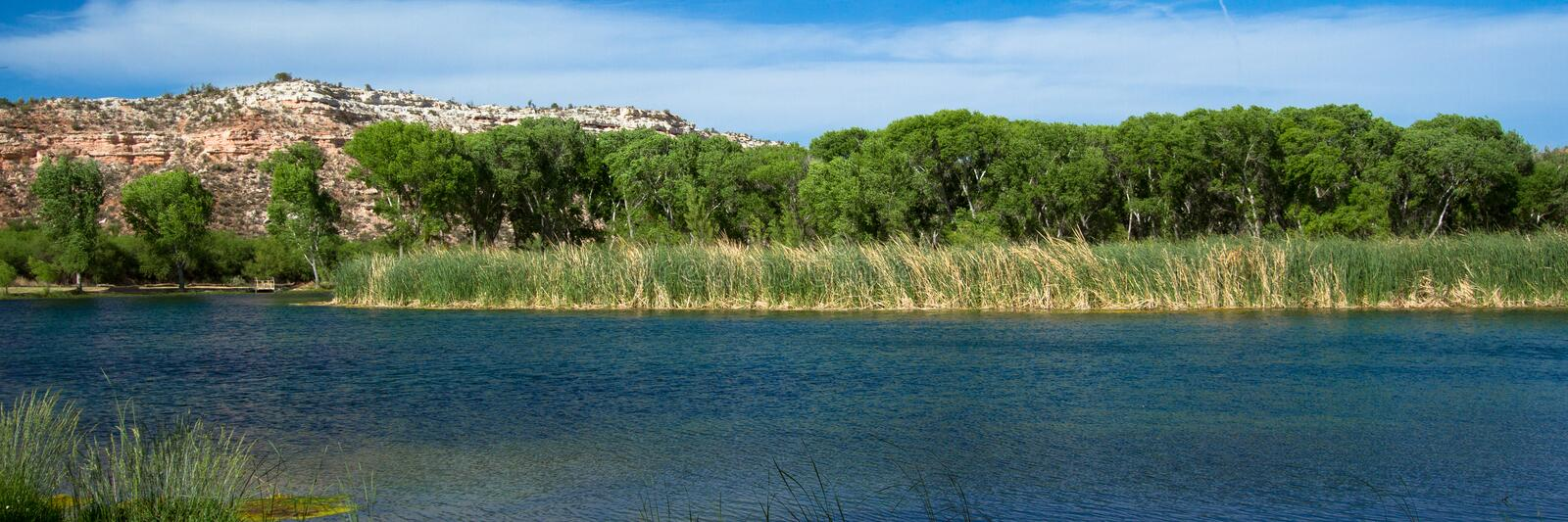 Water from the Verde River fills the lagoon, or marsh, at Dead Horse Ranch State Park near Cottonwood, Arizona. Panorama of a lagoon filled with water from the royalty free stock image