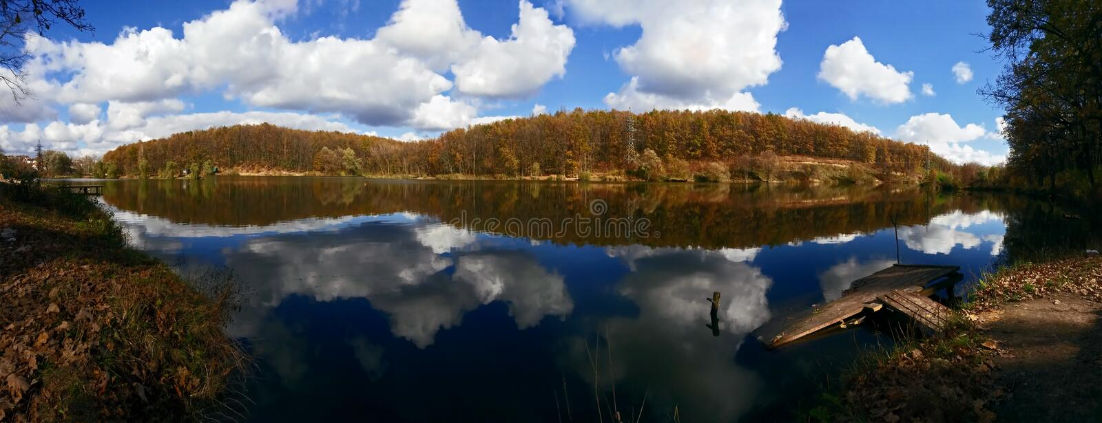 Panorama of lake in the autumn forest royalty free stock images
