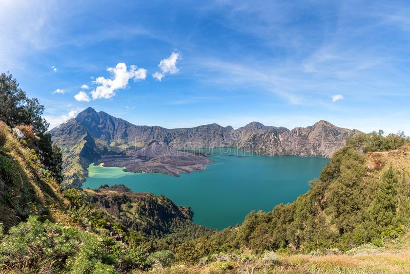 Panorama landscape of active volcano Baru Jari, Lake Segara Anak and summit of Rinjani mountain. Lombok island, Indonesia stock photo