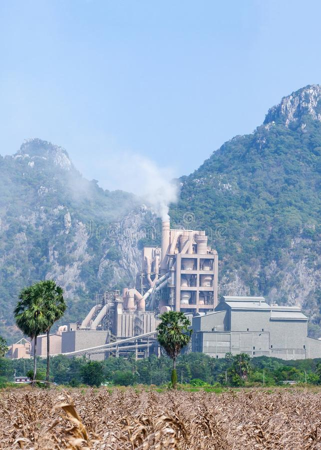Panorama landscape of cement factory in thailand, corn fields foregrounds, limestone mountain range backgrounds stock image