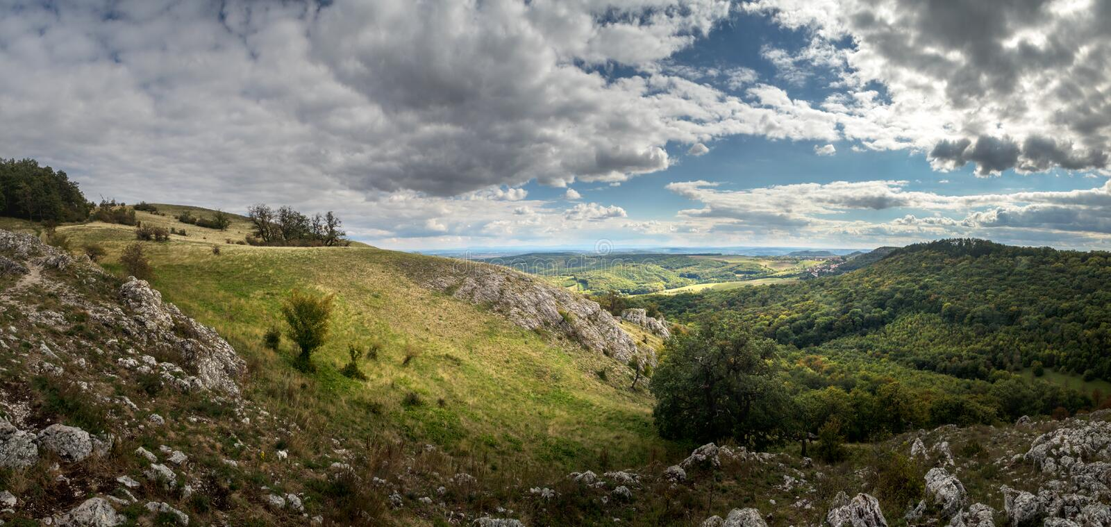 Panorama landscape with forested hills and rocks, cloudy sky stock image
