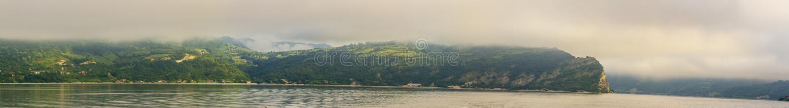 Panorama of landscape in Iron Gate. Panorama of landscape shrouded in fog cruising through the Iron Gate gorges on the Danube River between Serbia and Romania stock photo