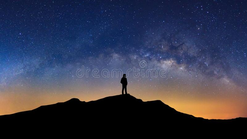 Panorama landscape with milky way, Night sky with stars and silhouette of a standing man on high mountain. stock image