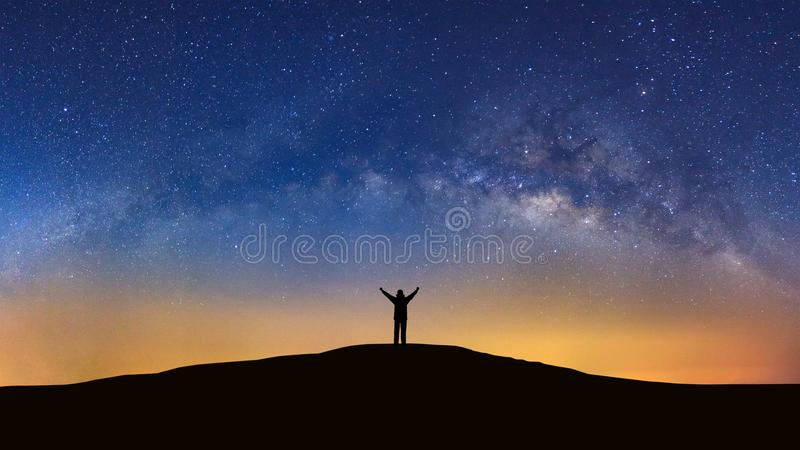 Panorama landscape with milky way, Night sky with stars and silhouette of a standing sporty man with raised up arms on high mount stock photo