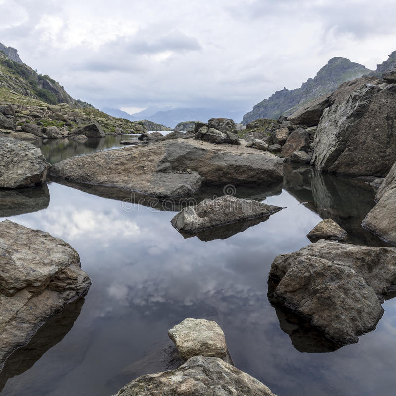 Free Panorama Landscape With A Lake In The Mountains, Huge Rocks And Stones On The Coast And Reflection Of Clouds Stock Images - 61031554