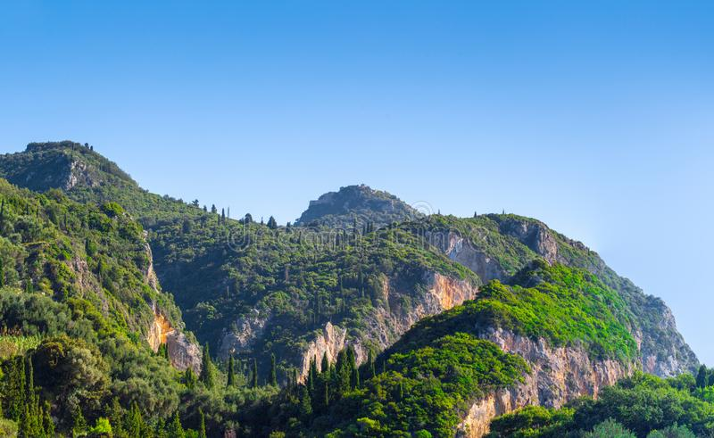 Panorama- landskap för härlig sommar Cypresskullar och gröna berglutningar Någonstans på Korfu Grekland driva som fiskar medelhav arkivfoto