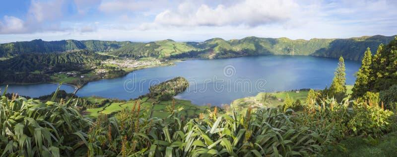 Panorama- landskapsikt av gröna och blåa kratersjöar av den Lagoa Azul och Lagoa Verde och Sete Cidades byn i arkivfoton